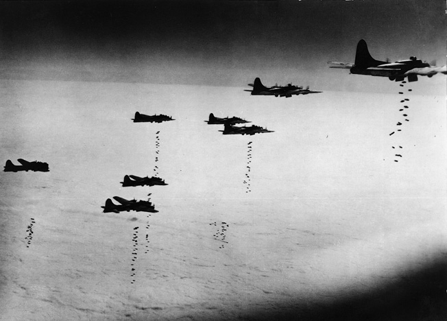 A tight formation of Eighth Air Force B-17s releases its bomb loads during a daylight raid over Betzdorf, Germany, March 12, 1945.