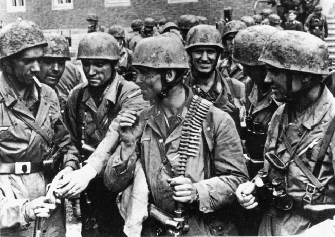 Wearing their iconic jump smocks and Fallschirmjäger helmets, a group of glider troopers relax after securing the victory.