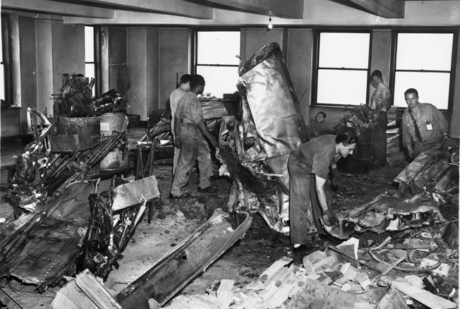 Workers sift through the ruins of the Catholic War Relief Services office, which took the full brunt of the plane's collision. Miraculously, the death toll was not higher than the 14 people killed.