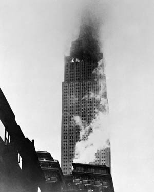 Smoke and flame are visible escaping from the 79th floor windows while fog obscures the upper floors of the Empire State Building following the crash.