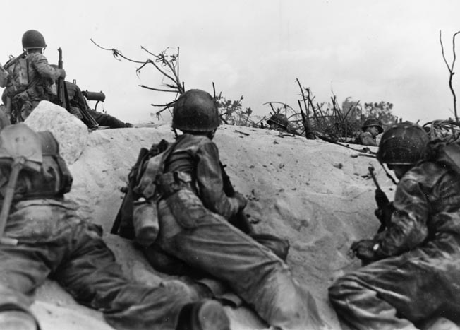 Marines from the 22nd Regiment, supported by a .30-caliber machine gun (upper left), find a bit of shelter in the coral sand of Parry Island prior to moving out to assault Japanese positions.