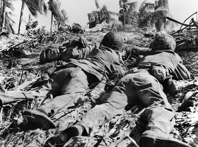 Taking cover behind the body of a dead Japanese defender, two Marine riflemen observe an enemy position. This image was taken by a Coast Guard photographer whose camera was later destroyed when he was blown into a foxhole by a Japanese mortar shell explosion.