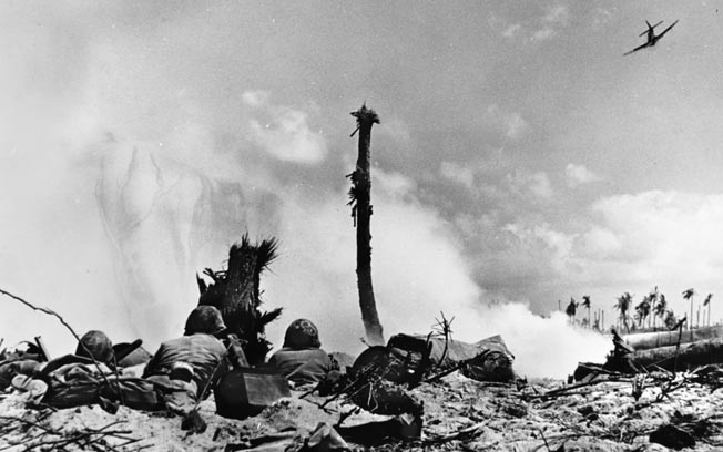 Three Marines on the lookout for snipers man a machine-gun position near a Japanese dugout on one of the islands of Eniwetok Atoll, while an SBD bomber makes a pass overhead, February 18, 1944.