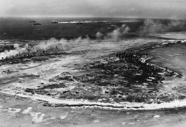 M-4 Sherman tanks (near bottom of photo) are visible moving across bomb-cratered Engebi Island during the last stages of fighting for the island. Japanese planes litter the airfield.