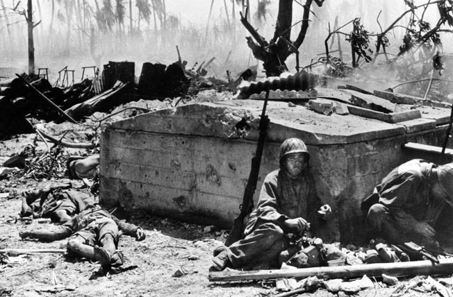 With dead Japanese lying outside a concrete bunker, an American serviceman takes a break from battle to grab a bite, February 20, 1944.