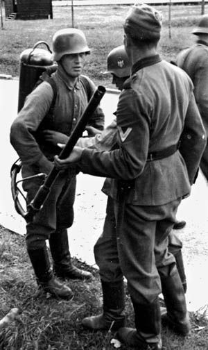 A soldier helps a comrade strap on a flamethrower unit prior to a training exercise.
