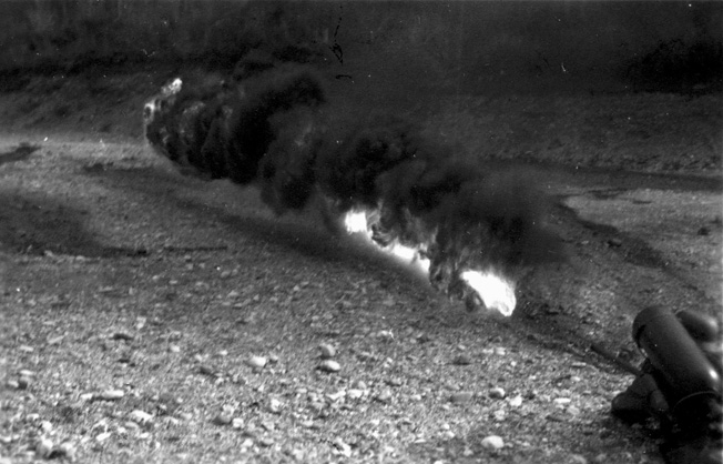 The range of the portable flamethrowers was approximately 20-25 yards, as shown in this training photograph.
