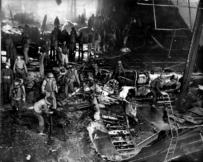 Crewmen survey the damage and look for survivors among destroyed aircraft on the USS Franklin.