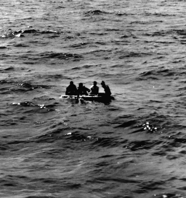 Survivors of the USS Franklin paddle in a raft thrown to them by the Santa Fe.