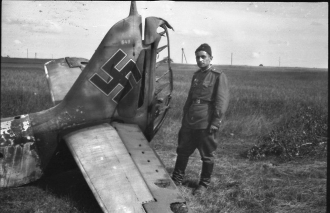 A Soviet mechanic inspects the wreckage of a German plane shot down on the Russian Front.