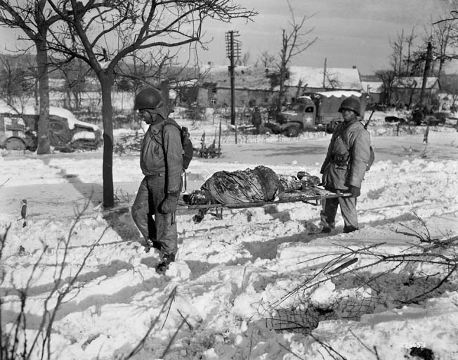 "An African American litter team from the 3200th Quartermaster Service Company, 24th Quartermaster Battalion carries a victim of the ""Malmedy Massacre"" from the snow-covered crime scene at Baugnez, Belgium."
