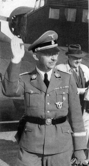 Exiting his personal Ju-52 aircraft during a tour of the Eastern Front, a smiling Himmler responds to a salute of soldiers. Behind him is his personal masseur and confidant, Dr. Felix Kersten.