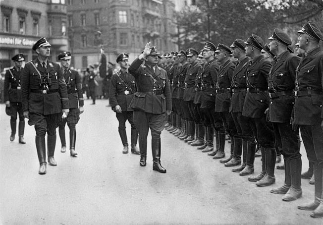 SA (Sturmabteilung) commander Ernst Röhm, with Himmler trailing, reviews a formation of SS troops in Berlin shortly before the SA chief's assassination in 1933. At this time, the SS was still subservient to the SA.