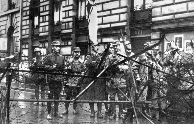 Heinrich Himmler, holding the imperial war flag, stands with other storm troopers at a Munich barricade during the Nazis' abortive November 9, 1923, attempt to overthrow the Bavarian government.
