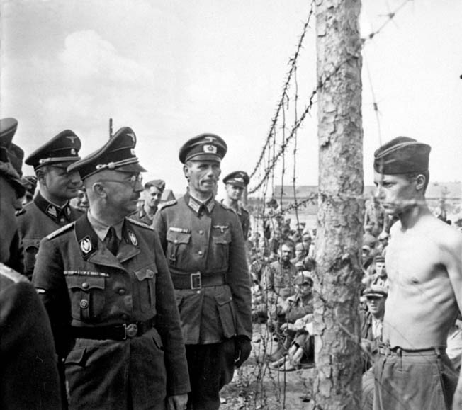 Himmler, accompanied by his entourage, inspects the Shirokaya Street camp in Minsk, Byelorussia, where thousands of captured Soviet soldiers were imprisoned, in August 1941. It was here that Himmler witnessed his first execution of a prisoner, an event that left him shaken.
