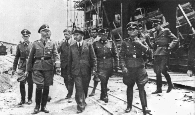 One of the Reichsführer-SS's duties was inspecting various facilities around the Greater Reich. Here, photographed in 1942, Himmler visits the I.G. Farben synthetic fuel and rubber plant at Monowitz-Buna (Auschwitz III), where thousands of slave laborers worked.