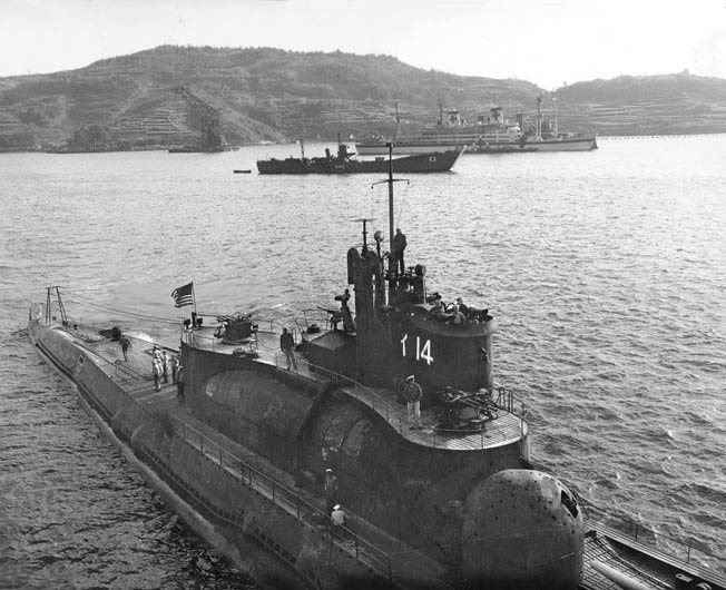 American naval personnel inspect the I-14, photographed in November 1945. The large structure beneath the conning tower was the hangar that could hold three planes with folded wings. The sub carried enough fuel to sail around the globe one and a half times.