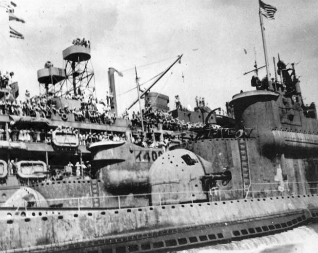 Sailors aboard the submarine tender USS Proteus (background) line the rails to view the I-400 and I-401 in Tokyo Bay, September 1945. The large rounded structure in the center of the photo is I-401's outer access door to the hangar.