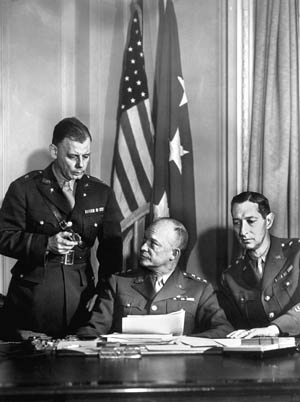 Ike meets with his chief of staff, Brig. Gen. Walter Bedell Smith (left) and Maj. Gen. Mark Wayne Clark, Ike's deputy and commander of II Corps.