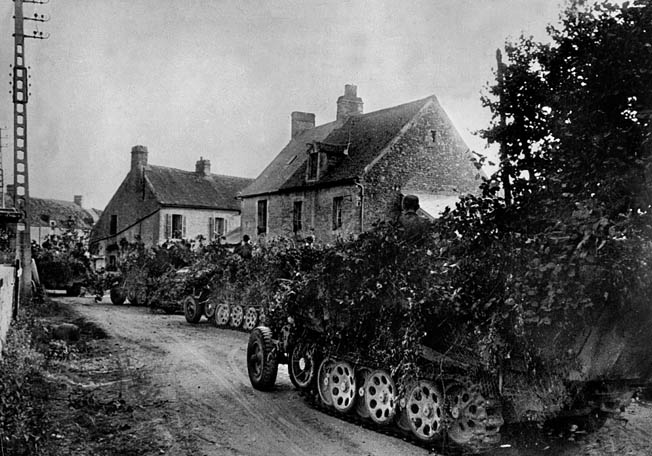 Camouflaged to avoid detection from the air, German SdKfz 7 half-tracked troop carriers move through a French village in hopes of breaking out of the encirclement.