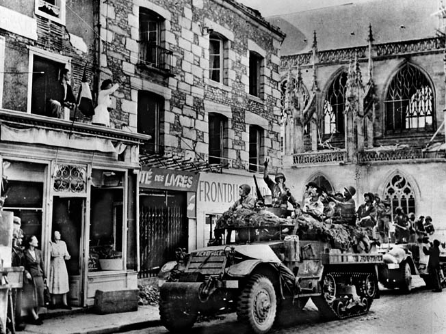 Greeted by cheering civilians, vehicles of the 2nd French Armored Division roll into Alençon on August 14, 1944.