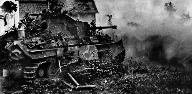 A German Panther tank fires as it moves into a Normandy village during the German counterattack.