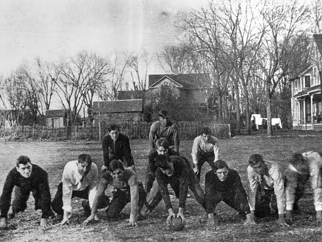 Wearing a white shirt and tie, Dwight Eisenhower (second from right) poses for a photo during a backyard football game in Abilene, Kansas (date unknown).