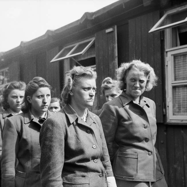 After the British liberated Bergen-Belsen on April 15, 1945, the female guards, shown here, were ordered to help bury the thousands of bodies. Pictured are Hildegard Kanbach (far left), Irene Haschke (center foreground), Head Wardress Elisabeth Volkenrath (second from right, partly hidden), and Herta Bothe (far right).