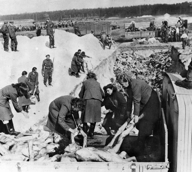 Women's work: British soldiers look on as Aufseherinnen at Bergen-Belsen are forced to dispose of 10,000 corpses in a mass grave.