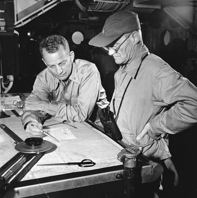 """Vice Admiral Marc A. """"Pete"""" Mitscher (right), commander of Carrier Task Force 58, studies charts with a staff officer."""