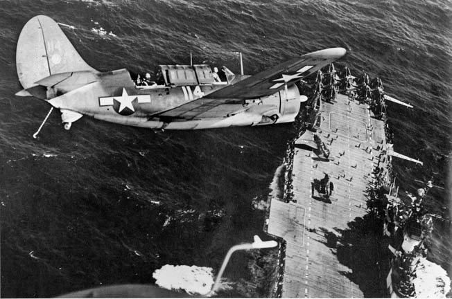 A Navy Helldiver banks over its aircraft carrier after strikes on Japanese shipping. Dive-bombing was pioneered by Navy pilots in the 1930s.