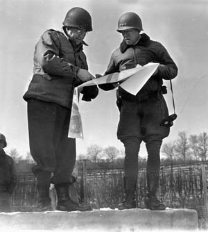 Maj. Gen. Manton S. Eddy (left), commanding U.S. XII Corps, talks strategy with Third Army commander Lt. Gen. George S. Patton, Jr., during the drive into the West Wall, December 1944.