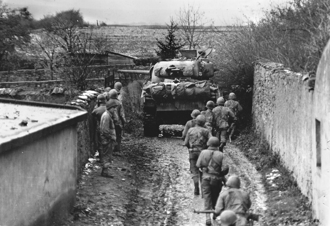 Infantrymen and a Sherman tank cautiously advance down a walled lane near Metz, November 1944, as German troops pull back.