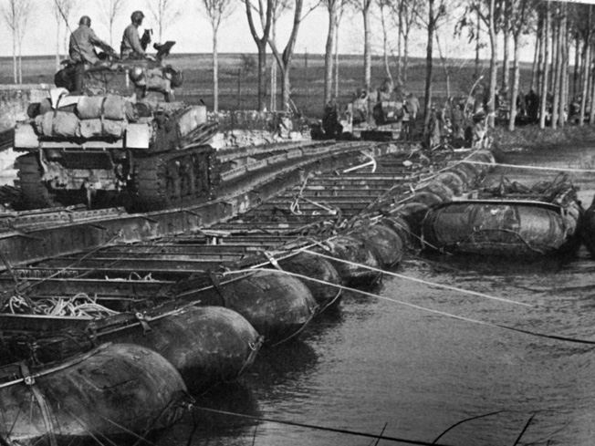 The many rivers and streams in Lorraine kept the combat engineer battalions busy building bridges. Here tanks of the 15th Tank Battalion, 6th Armored Division, cross a pontoon bridge over the Seille River at Port-sur-Seille, between Metz and Nancy.