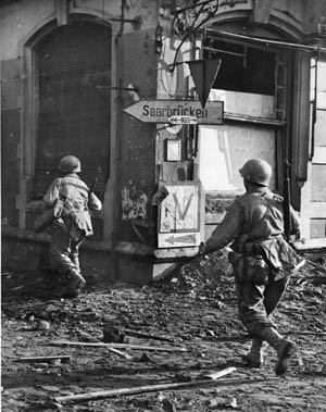 American troops of XII Corps move through the rubble of St. Avold, a key communications center of the German 19th Army. The town was captured by Third Army units on November 27, 1944.