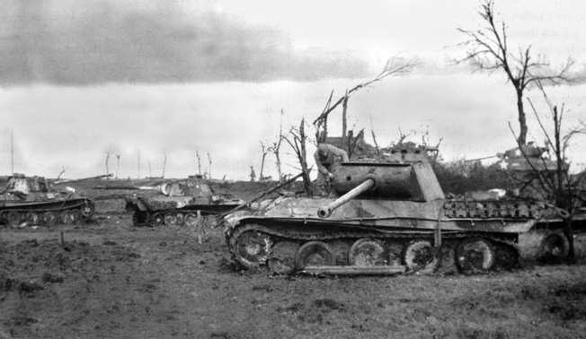 An American soldier of the 4th Armored Division inspects one of three German panzers of the 11th Panzer Division knocked out during fighting near Guébling, France, about 30 miles southeast of Metz, on November 14, 1944.