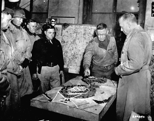 Using a model of the Metz area to brief visiting brass at his headquarters on November 10, 1944, is 5th Infantry Division Commanding General S. Leroy Irwin. Among the visitors are Lt. Gen. Thomas T. Handy, the Army's Deputy Chief of Staff (left) and Lt. Gen. George S. Patton, Jr. (second from left). Army Chief of Staff General George C. Marshall is at right.