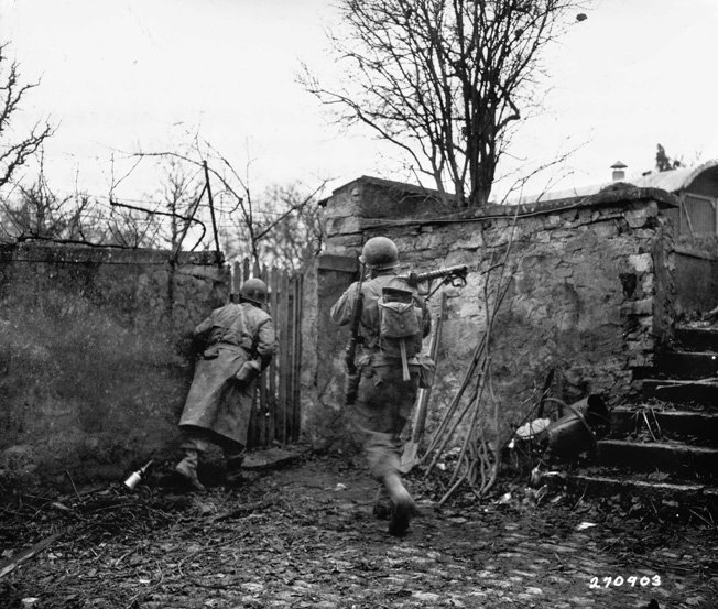 An officer from the 26th Infantry Division peers around a wall in Sarre-Union, France—east of Metz—as one of his men brings up a .30-caliber machine gun.