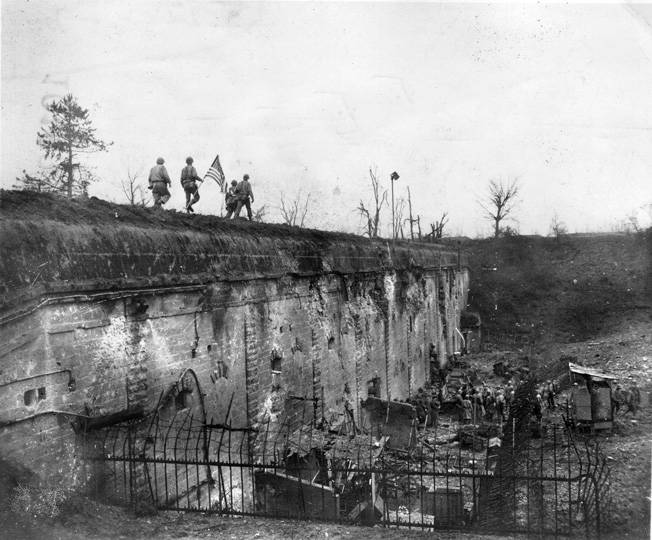 Soldiers from the 26th Infantry Division carry an American flag to plant atop the ramparts after Fort Jeanne d'Arc, the last German-held fort at Metz to capitulate.