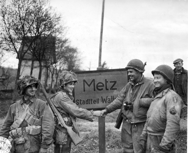Members of the 5th and 95th Infantry Divisions shake hands after sealing off the last escape route of German troops in Metz, November 22, 1944.