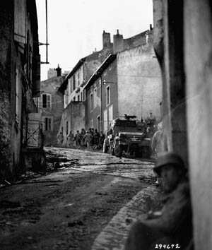 Men of the U.S. 5th Infantry Division hug the walls in one of the suburbs of Metz in early September 1944. Patton's rapid advance across France came to an abrupt halt at Metz, due to fuel shortages, deteriorating weather conditions, and increased enemy resistance.