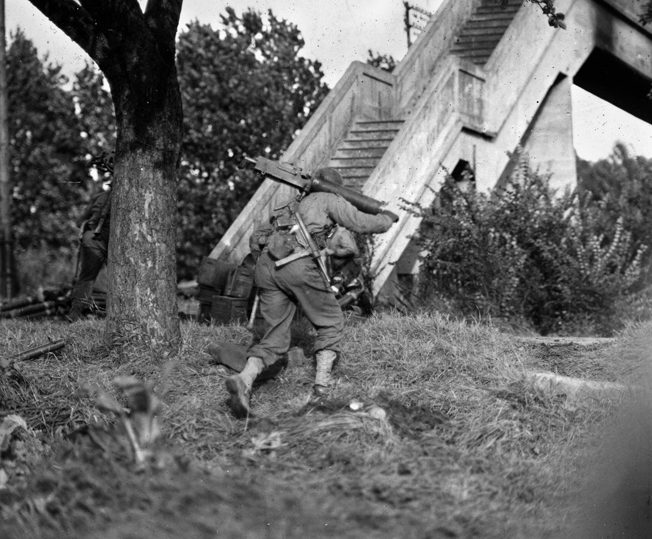 """An American soldier, carrying a .30-caliber Browning water-cooled machine gun M1917A1 in addition to his personal M3 .45-caliber sub-machine gun (aka """"grease gun"""") moves into position near Metz."""
