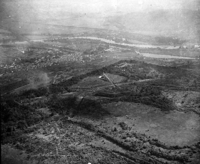 Aerial view looking toward the east, showing Fort Driant (foreground); the Moselle River is visible in the distance. Located high on a forested bluff southwest of Metz, Fort Driant, with its heavy guns, thick concrete casemates, and labyrinth of tunnels, was one of more than a dozen fortifications dating from the 1800s that guarded the southern approaches to the city.