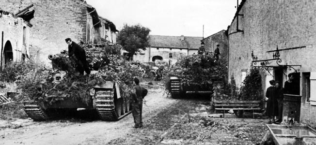 RETREAT FROM FRANCE, 1944.  German tanks, camouflaged against attacks from the air, in a village on the Moselle River in France after the Allied invasion of Normandy. World War II, German army photograph, autumn 1944.