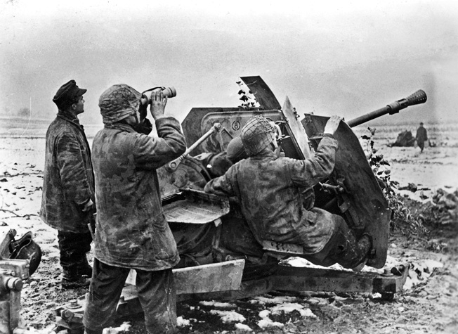 German troops manning a 3.7cm Flak 36/37 anti-aircraft gun in the Saarland are on the alert for an American aerial assault, December 1944.