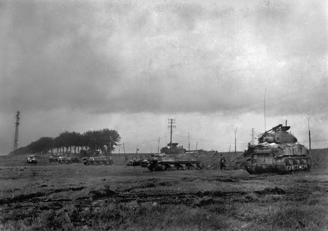 To defend against the more heavily armored German tanks, American armor takes cover behind an embankment near Moncel, France. Overhead, P-47s surprised the German tanks and helped drive them off.