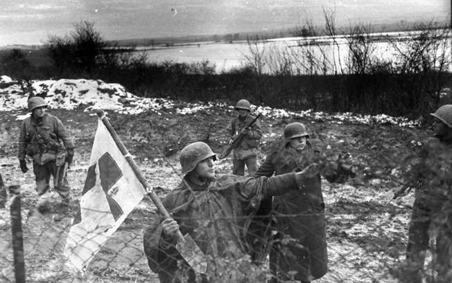 Two German medics, carrying a Red Cross flag for protection, surrender to American troops at Metz, November 22, 1944.