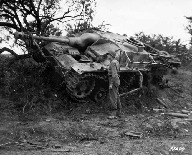 A GI examines a knocked-out StuG IV near Lunéville, France. The StuG IV had no rotatable turret; the entire vehicle had to be aimed in the direction of the target.
