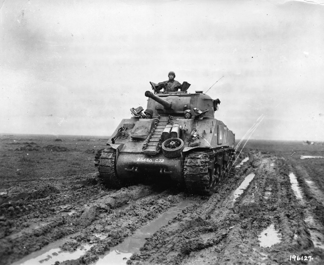 "An M-4 Sherman tank, outfitted with track extenders (known as ""duck bills"") for better traction in muddy conditions, crosses a rain-soaked field near Metz."