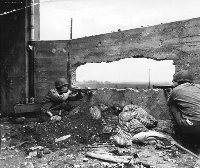 A 90th Infantry Division GI with a Browning Automatic Rifle (BAR) and his buddy with an M-1 Garand keep a sharp lookout through a hole blasted in a concrete wall near the town of Maizieres-les-Metz, October 1944.